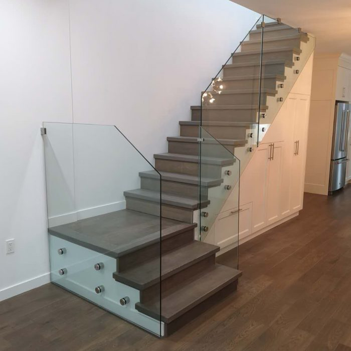 Contemporary wooden staircase with glass railing remodel project in oakville Fuda Homes