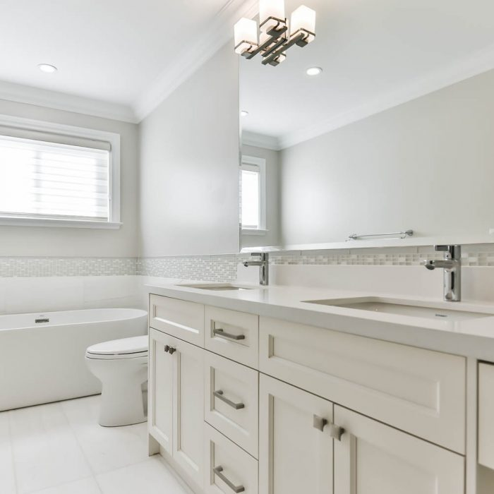 contemporary master white tile bathroom remodel in Oakville with an undermount sink white cabinets quartz countertops and shaker panel cabinets Fuda Homes
