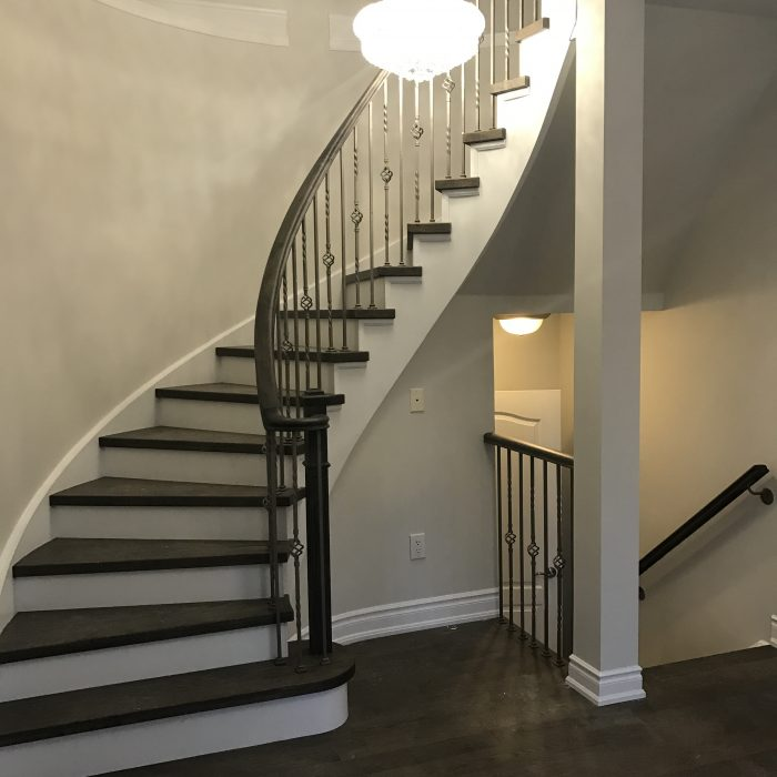 large transitional painted curved mixed material railing staircase design in Mississauga with painted risers